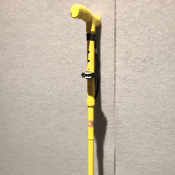 Infront of a fabric covered wall is the top top half of a walking stick. It is bright yellow and has ablack fabric wrist strap, a black and white frog bracket that helpd it balance on tables and an orange sticker